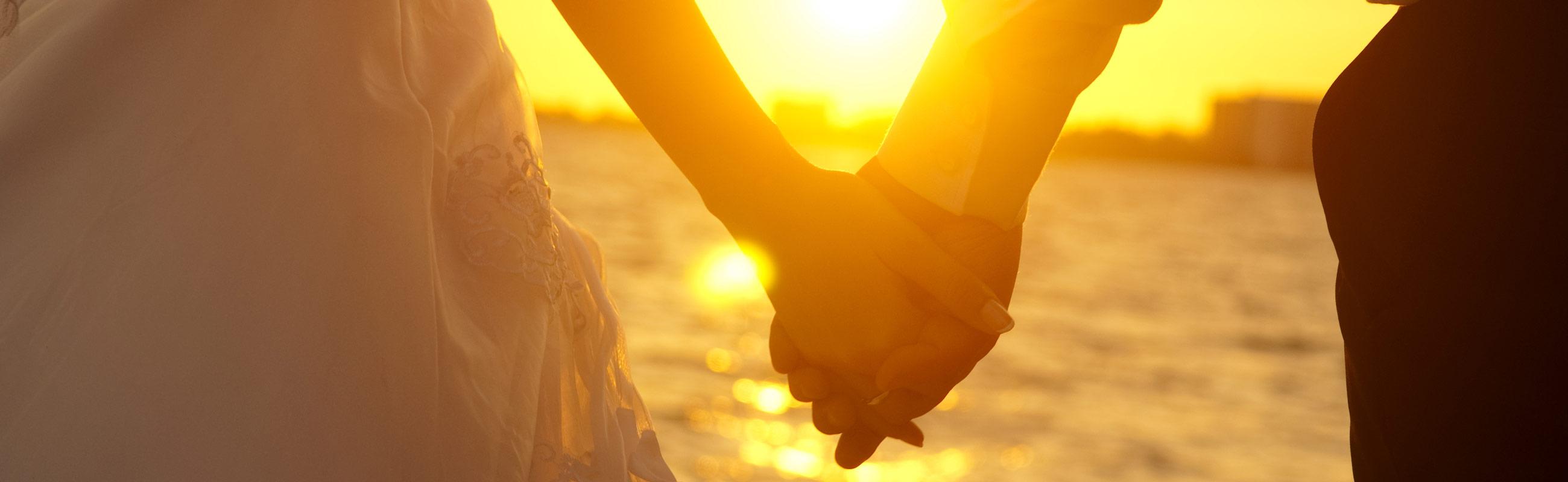 bride groom holding hands in front of the ocean
